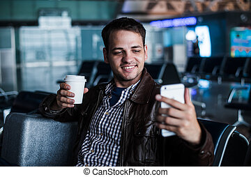 Portrait of a young man laughing and taking selfie with coffee at the airport waiting his flight