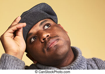 Portrait of a young man of African descent with a cap daydreaming (Selective Focus, Focus on the eyes)