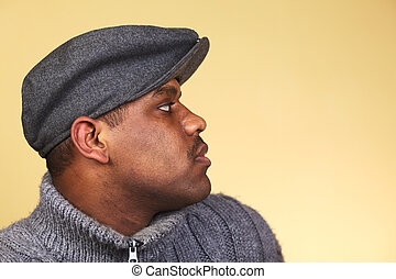 Portrait of a young man of African descent with a cap (Selective Focus, Focus on the eye)