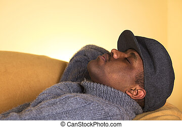 Portrait of a young man of African descent taking a nap on a sofa (Selective Focus, Focus on the left eye)