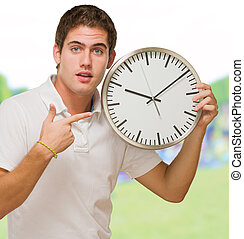Portrait Of A Young Man Pointing at a Wall Clock