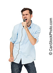 Portrait of a young man singing into microphone