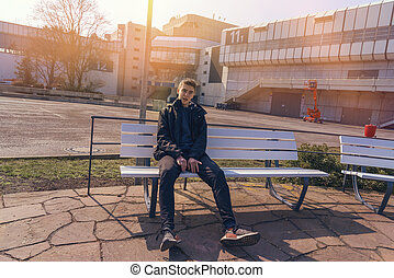 portrait of a young man sitting on a bench