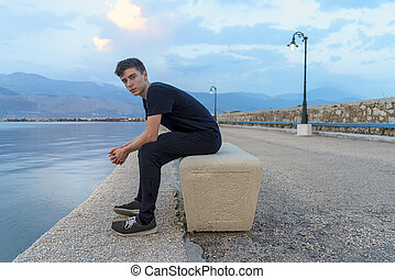 portrait of a young man sitting on a pier