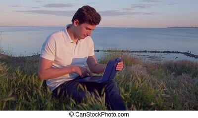 Portrait of a young man sitting on a hillside near the sea