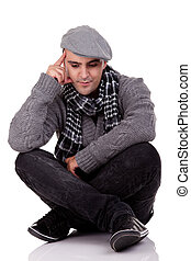 Portrait of a young man sitting on the floor, thinking and looking down, in autumn/winter clothes, isolated on white, Studio shot
