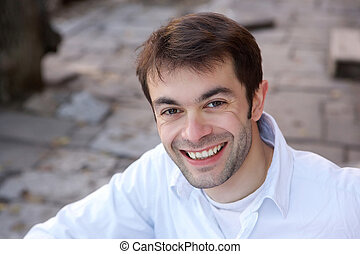 Portrait of a young man smiling outdoors