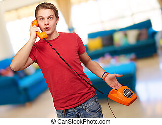 Portrait of a young man talking on vintage phone