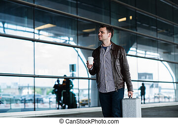 Portrait of a young man walking near the airport with suitcase and coffee