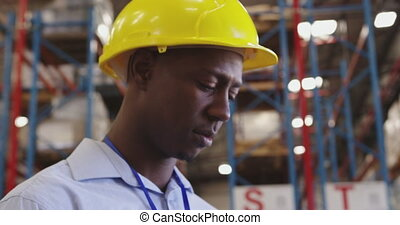 Portrait of a young man wearing a hard hat in a warehouse 4k...