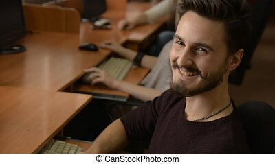Portrait of a young man with a beard smiling. A business man...