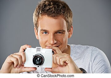 Portrait of a young man with a camera