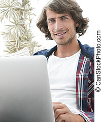 Portrait of a young man with a laptop sitting in a chair