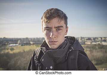 portrait of a young man with a panorama of houses in background