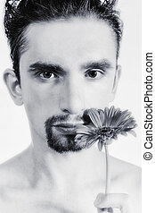 Portrait of a young man with gerberas in a hand