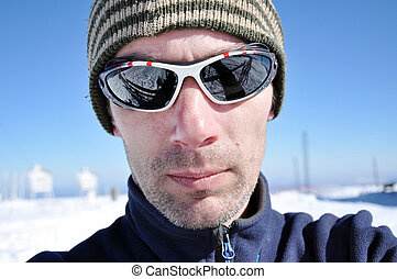 Portrait of a young man with sunglasses at winter