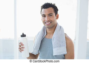 Portrait of a young man with towel around neck holding water bottle in fitness studio