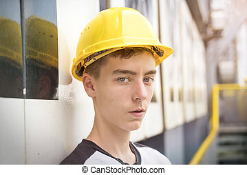 portrait of a young man with yellow safety helmet