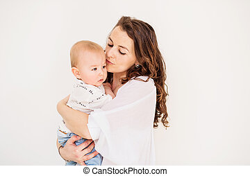 Portrait of a young mother kissing her baby son at home. Copy space.