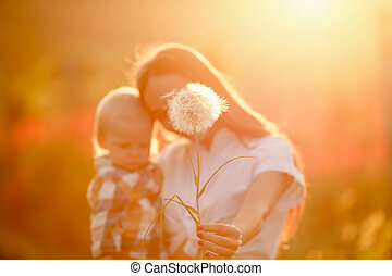 portrait of a young mother with a child in her arms in one hand and in the other a large dandelion with white petals
