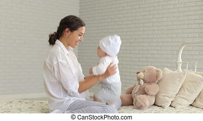 Portrait of a young mother with a newborn baby at home on the bed.