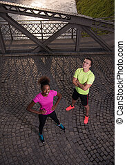 portrait of a young multiethnic couple jogging in the city