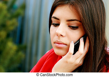 Portrait of a young pensive woman talking on the phone