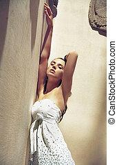 Portrait of a young pretty brunette posin in a stylish interior