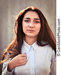Portrait of a young pretty girl in a light shirt and with her ha