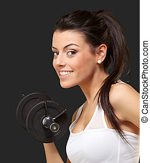 portrait of a young pretty woman holding weights and doing fitness against a black background