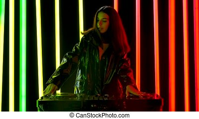Portrait of a young pretty woman in big red headphones plays turntables electronic dance music and dances. Brunette poses against a dark studio background with bright multicolored neon tubes. Slow motion.