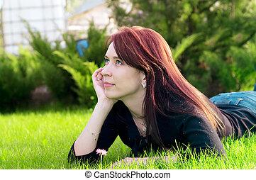 pretty woman lying on green grass
