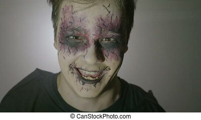 Portrait of a young psychopath zombie man with strange eyes and face paint doing frightening halloween moves