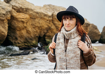 Portrait of a young red-haired woman in a hat and a scarf with a backpack against the background of the rocks against the beautiful sea, on the coast, on the horizon. Tourism, rest, lifestyle.