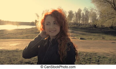 portrait of a young red-haired woman outdoors