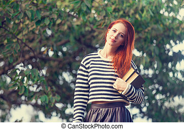 Portrait of a young redhead girl with books