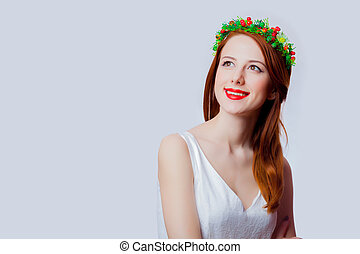 Portrait of a young redhead girl with flowers wreath
