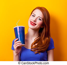 Portrait of a young redhead girl with movie cola