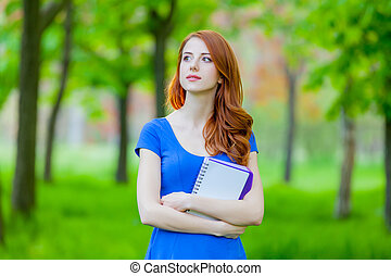 Portrait of a young redhead girl with notes
