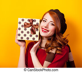 Portrait of a young redhead girl with present box