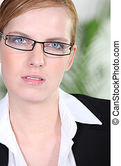Portrait of a young redhead woman with eyeglasses