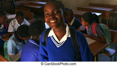 Portrait close up of a young African schoolboy wearing his school uniform and schoolbag, looking up to camera smiling, at a township elementary school with classmates sitting at desks in the background 4k