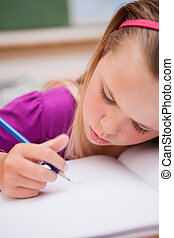 Portrait of a young schoolgirl writing