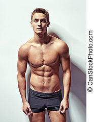 Portrait of a young sexy muscular man in underwear against...
