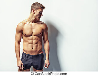 Portrait of a young sexy muscular man in underwear looking...