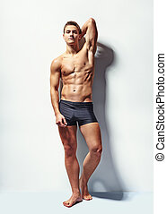 Portrait of a young sexy muscular man - Full length portrait...