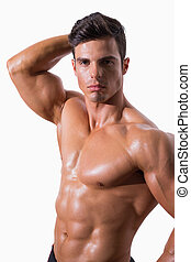 Portrait of a young shirtless muscular man posing over white...