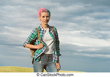 portrait of a young smiling attractive woman in plaid shirt clothes with small backpack at sunny day on the cloudy sky and field background. joyful woman posing in landscape on sunset