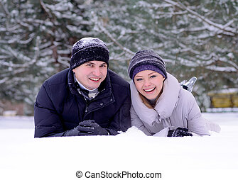 Portrait of a Young Smiling Couple Lying on the Snow
