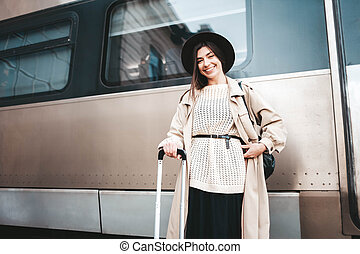 Portrait of a young smiling girl traveler on the background of a passenger train cars